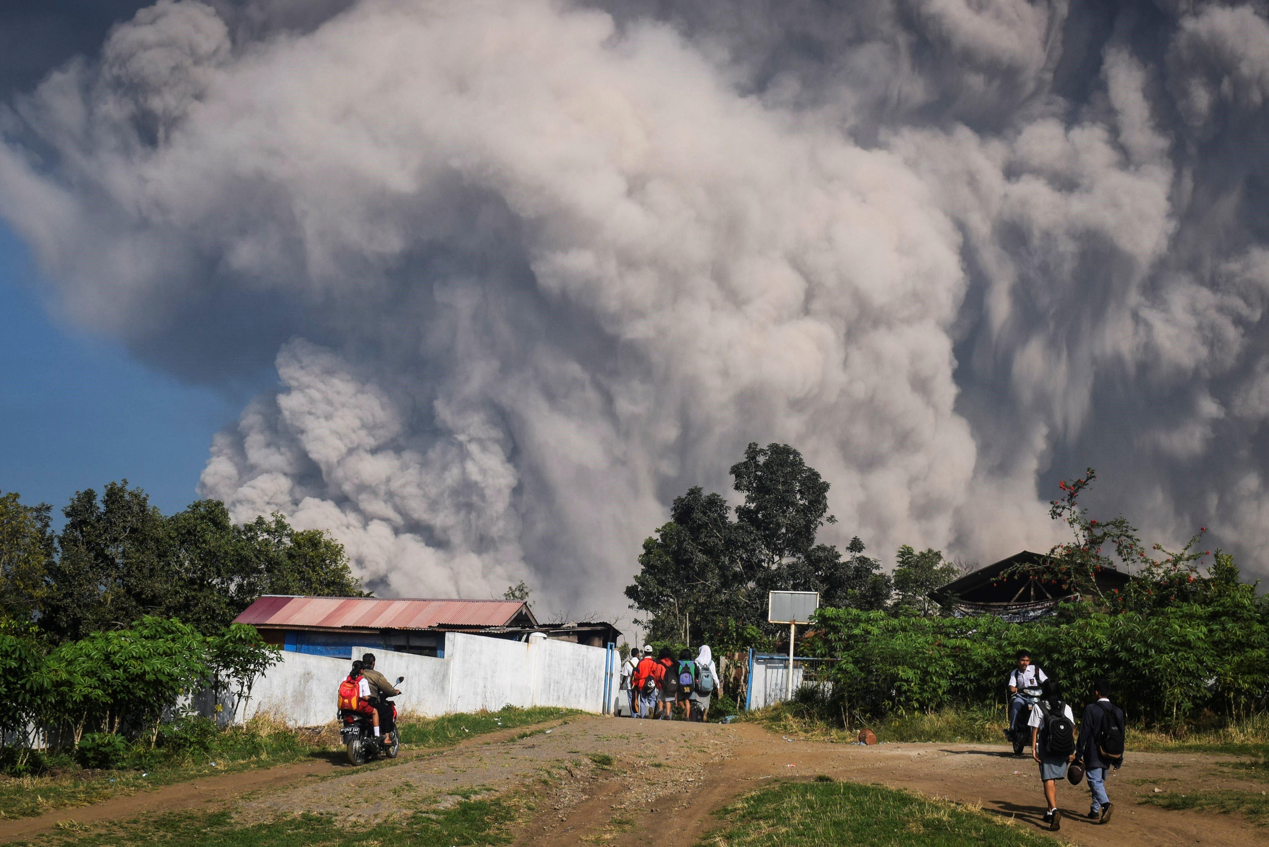 Diversos estudiants caminen prop d'un núvol de cendres volcàniques a Karo, Sumatra Nord (Indonèsia). /SARIANTO OJO SEMBIRING