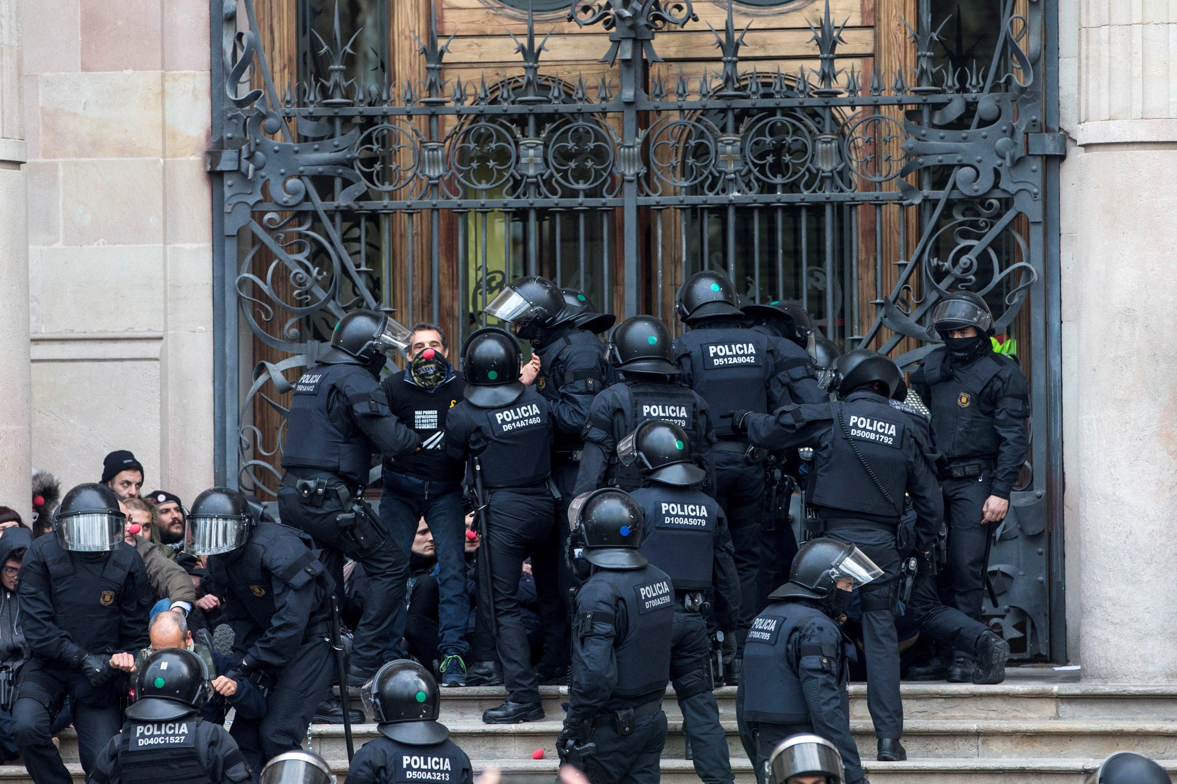 Agents dels Mossos d'Esquadra desallotgen les desenes de persones que s'han concentrat a primera hora d'aquest divendres davant el Tribunal Superior de Justícia de Catalunya (TSJC) en protesta per les actuacions de la justícia en la crisi catalana i exigint la llibertat dels polítics empresonats. /QUIQUE GARCÍA
