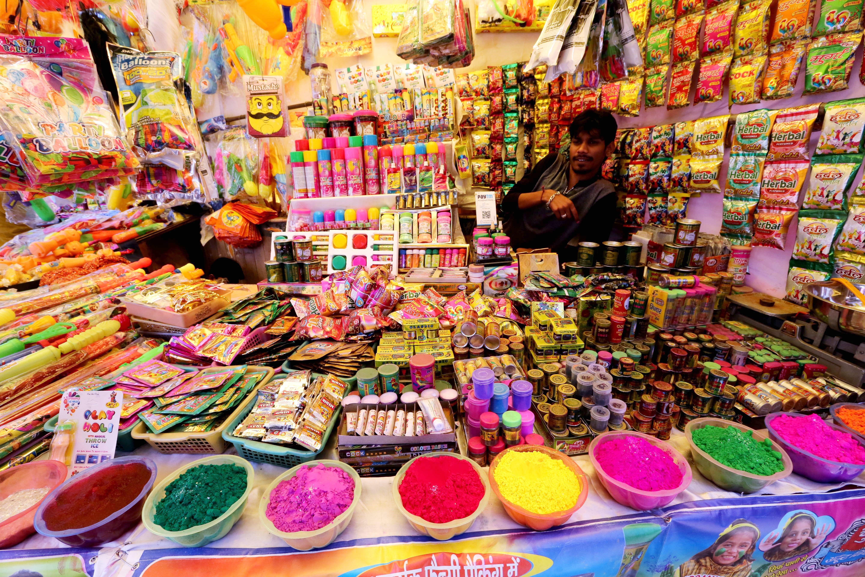 Una dona ven pólvores de colors en un mercat per a la celebració Holi a Bhopal (Índia). /SANJEEV GUPTA