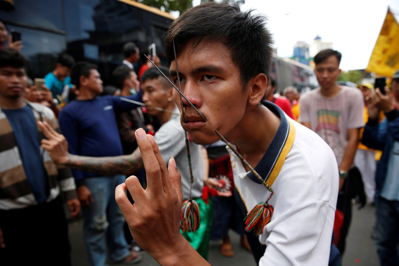 Un jove indonesi d'origen xinès es perfora els queixos amb dos pinxos metàl·lics durant la celebració del festival Cap Go Meh a Jakarta, Indonèsia. /ADI WEDA