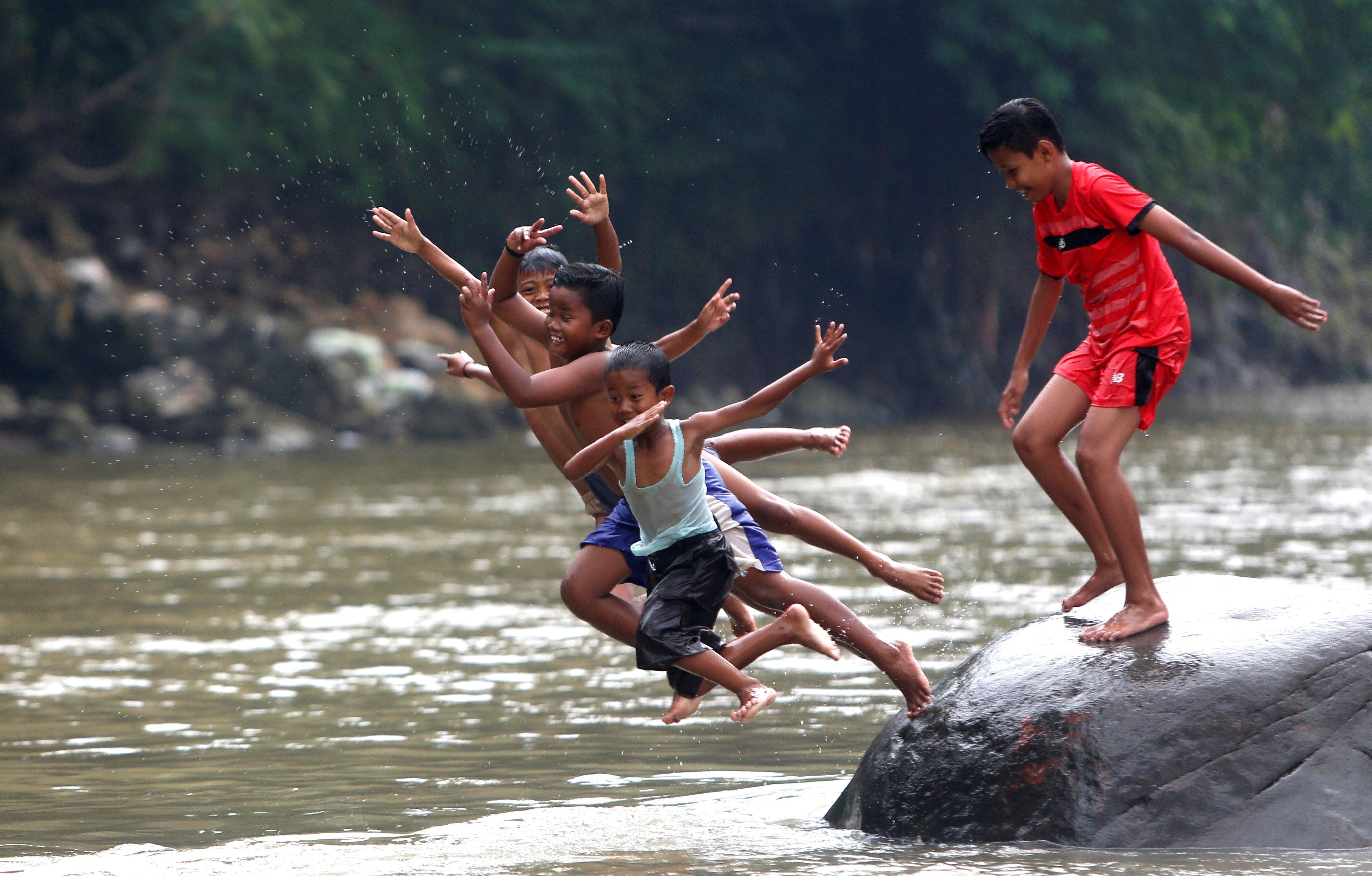 Un grup de nins juga al riu Ciliwung el Dia Mundial d'Acció en Defensa dels Rius, a Bogor, Indonèsia. /ADI WEDA