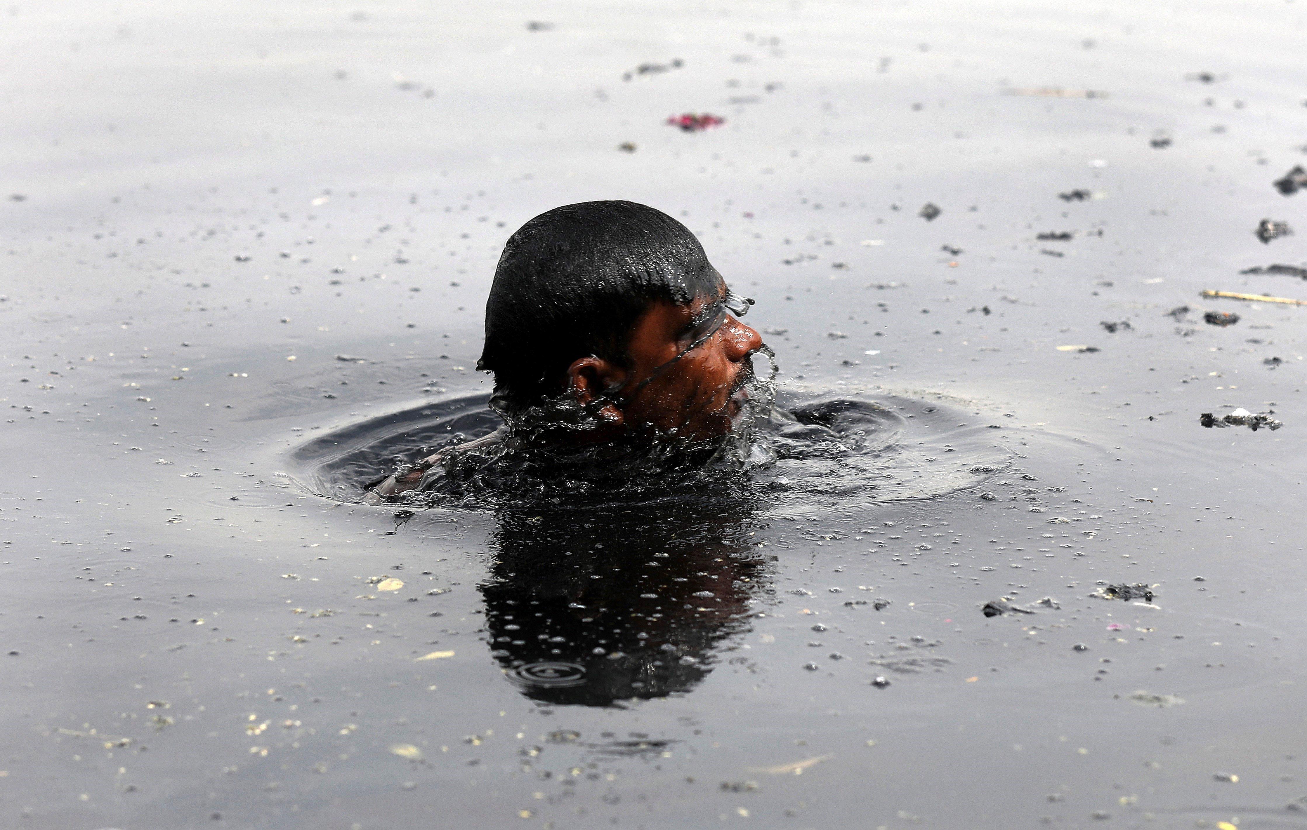 Un home se submergeix en el riu contaminat de Yamuna a la recerca de monedes que llancen els devots en una espècie de ritual, a Nova Delhi, Índia. /RAJAT GUPTA