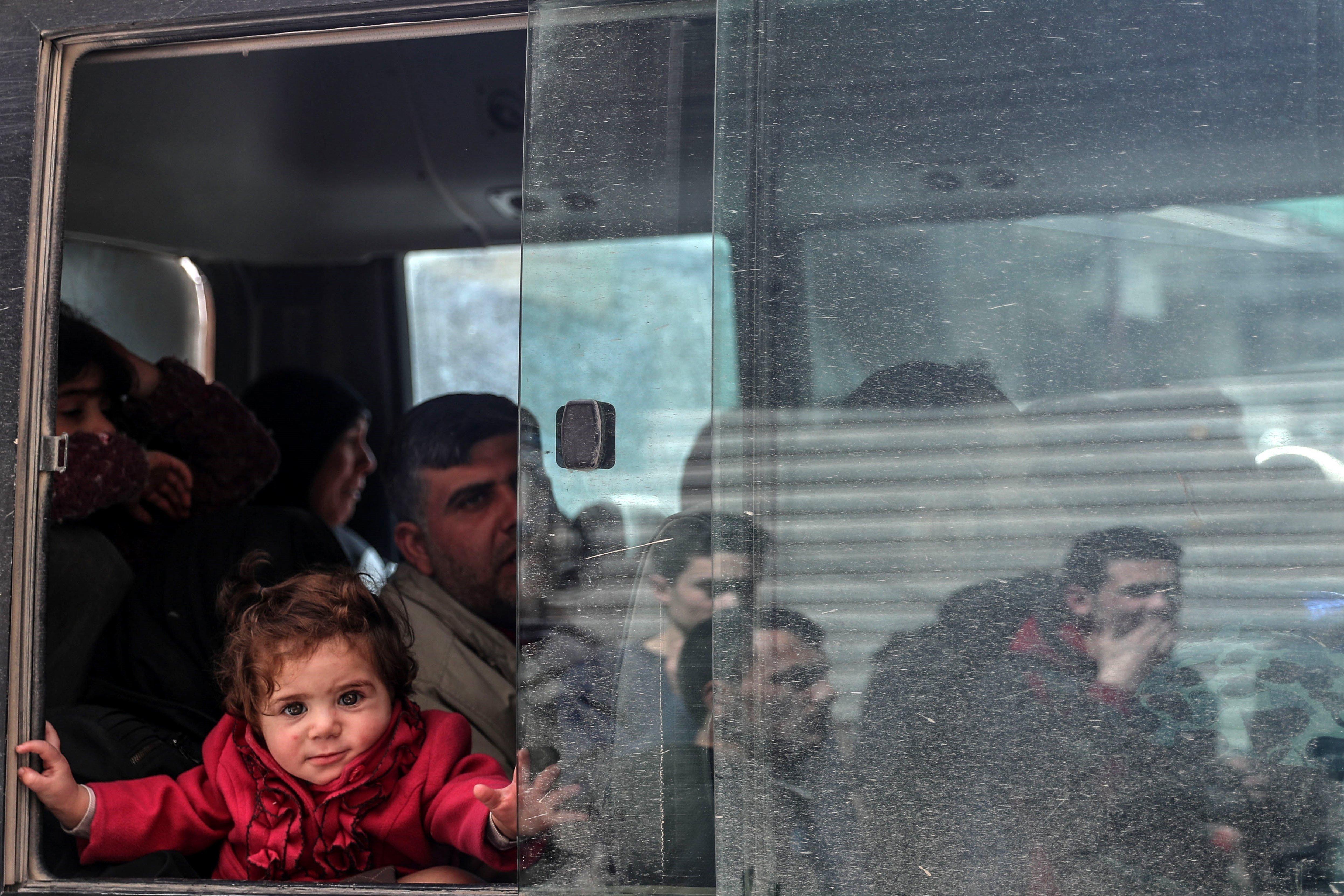 Una nina observa al fotògraf des d'un autobús durant el segon dia de l'evacuació de Duma (Síria). /MOHAMMED BADRA