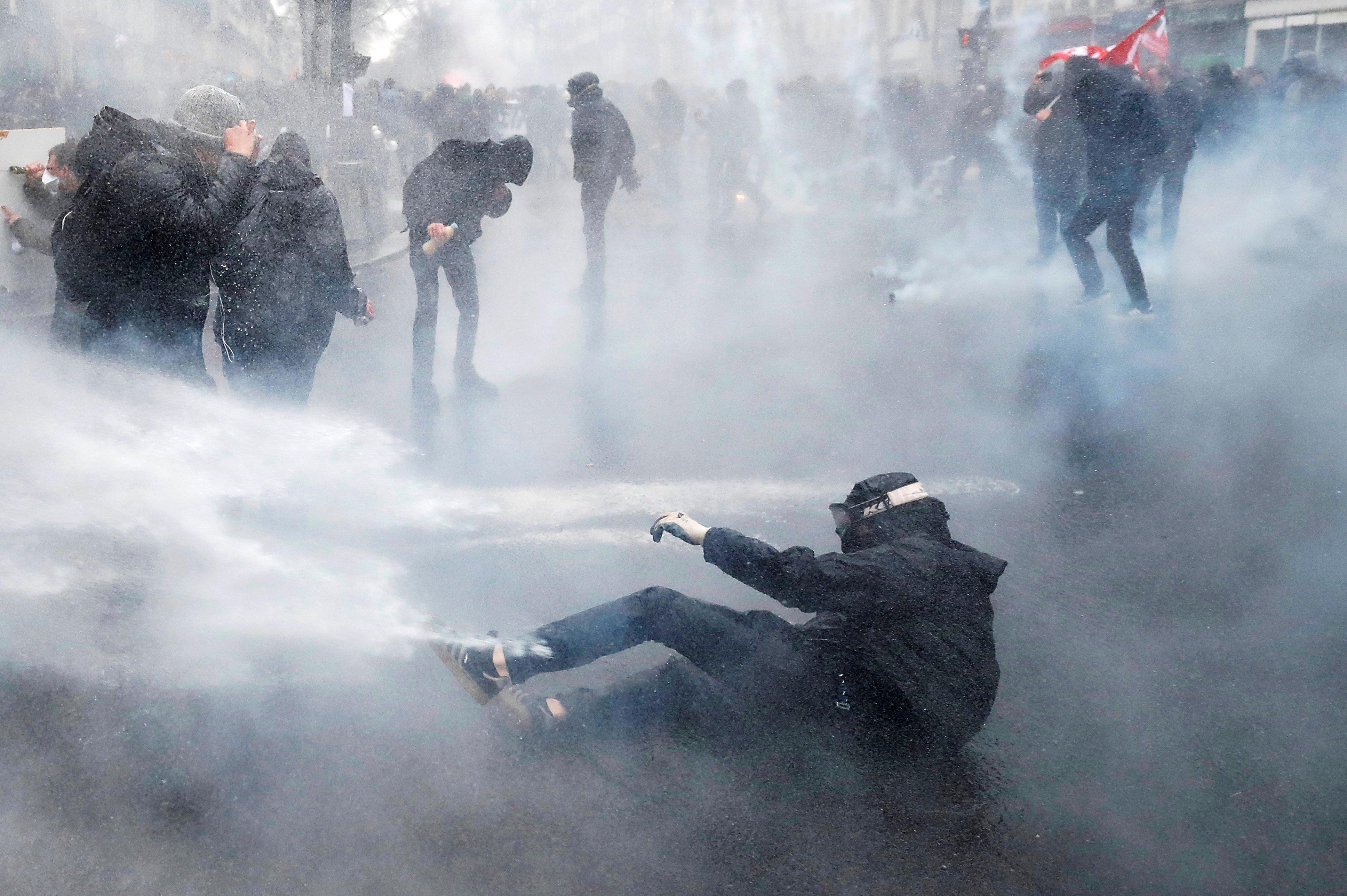 La policia antidisturbis dispersa amb canons d'aigua manifestants durant la vaga general dels serveis públics i transports a París (França). /YOAN VALAT