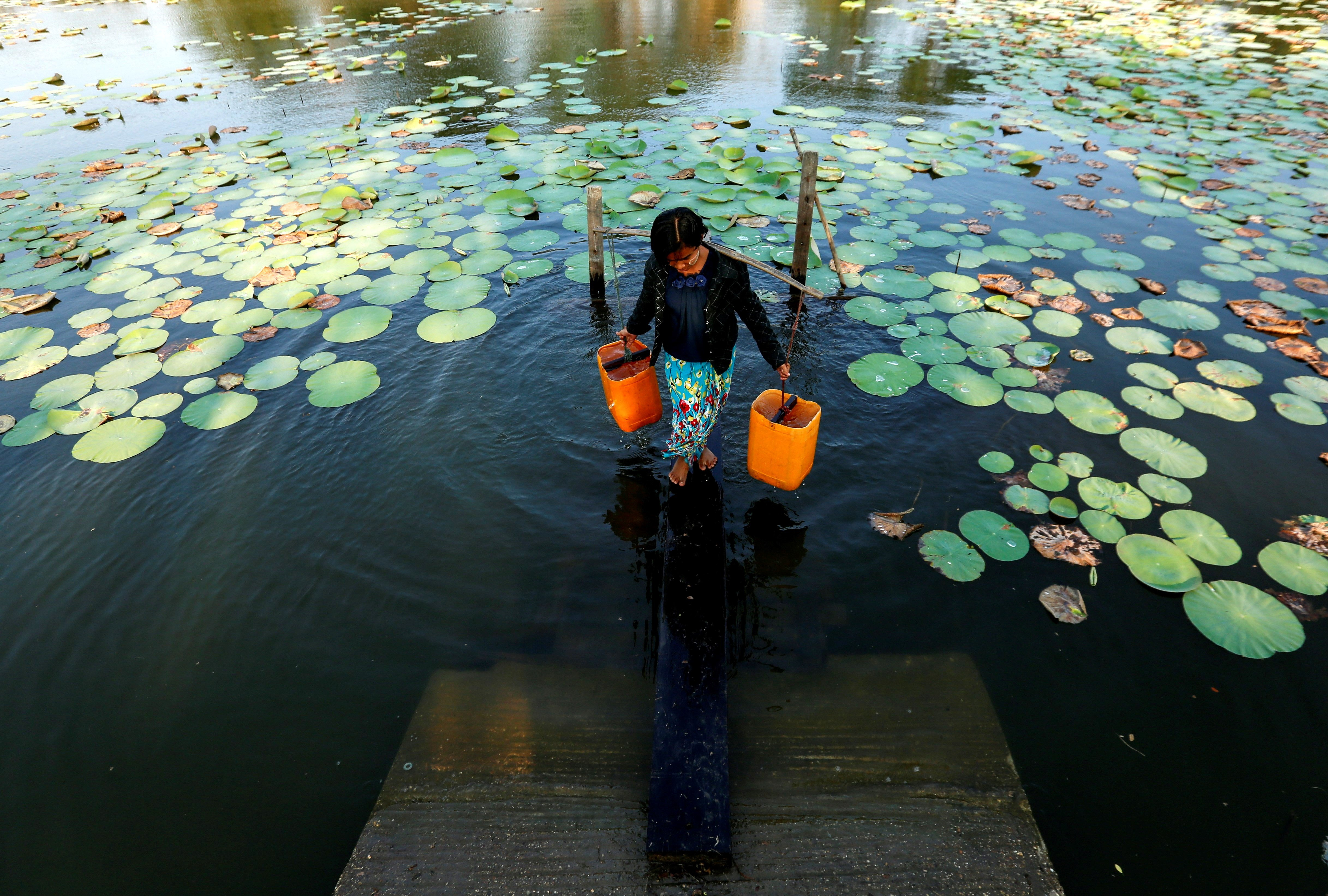 Una dona recull aigua d'un estany a Dala (Birmània) on el sistema de distribució d'aigua és molt limitat. /LYNN BO BO