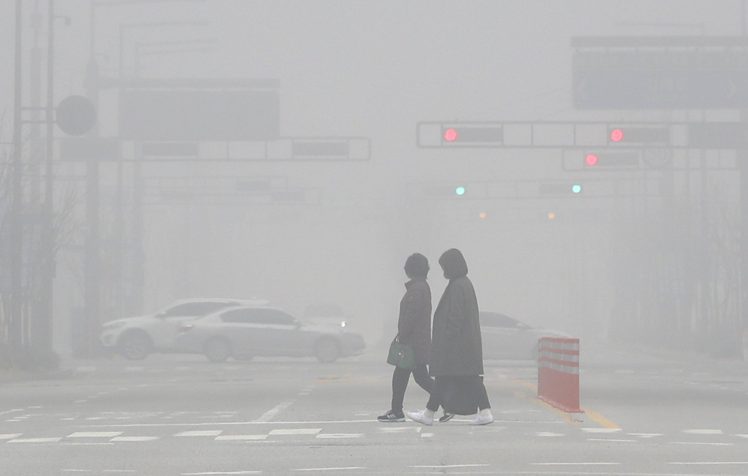Persones caminen enmig de la boira de contaminació als carrers de Sejong. /YONHAP