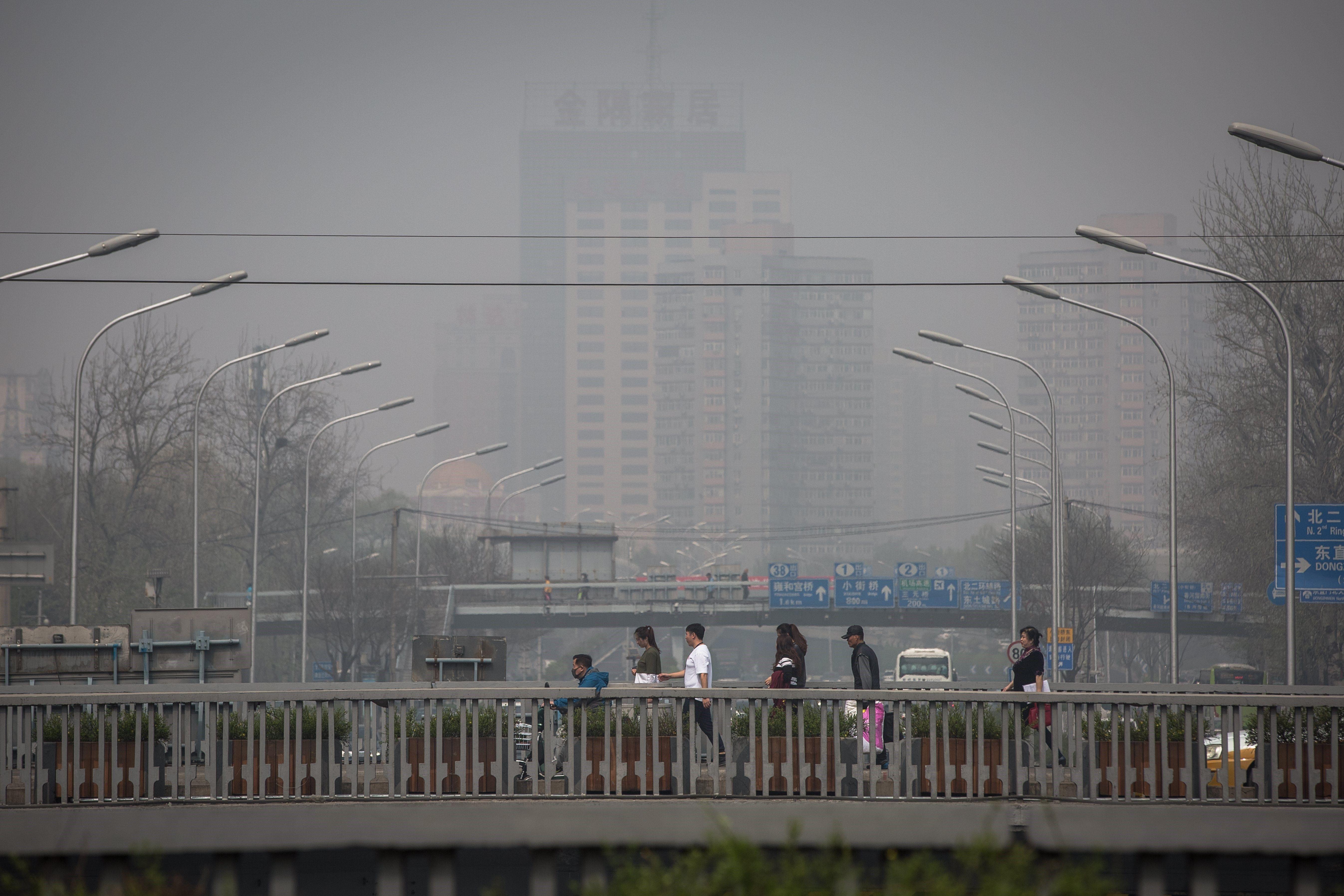 Diverses persones creuen un pont mentre una capa de pol·lució embolica uns edificis a Pequín (Xina). /ROMAN PILIPEY