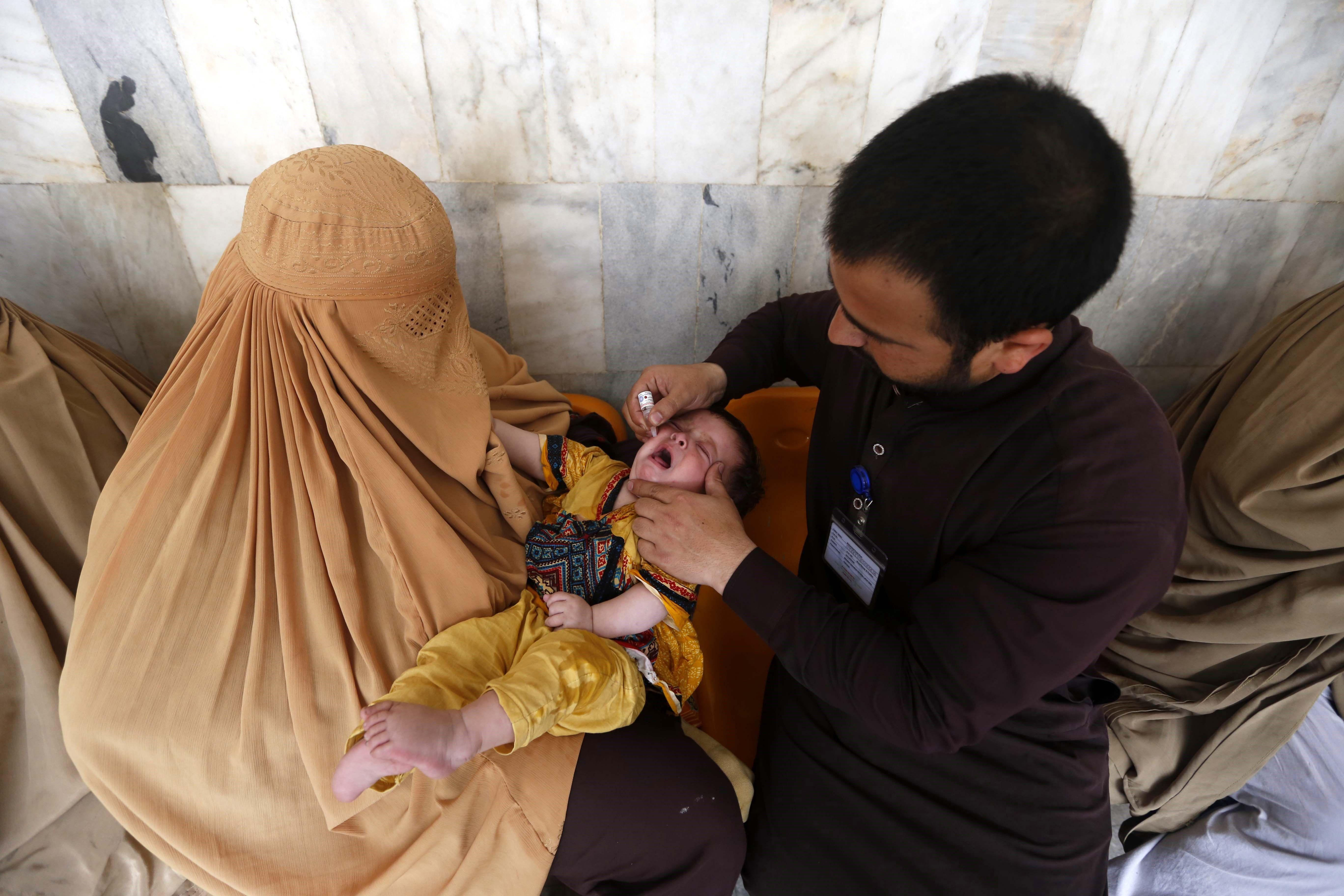 Membres d'un equip sanitari administren vacunes contra la pòlio a un nin durant la campanya de vacunació, de tres dies de durada, a Peshawar, Pakistan. /ARSHAD ARBAB