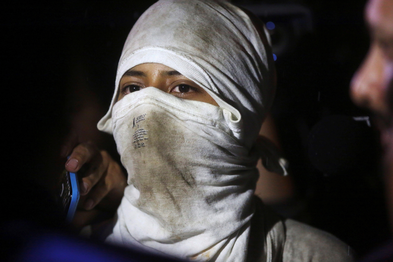 Un menor amb el rostre cobert parla amb el procurador dels Drets Humans a Guatemala Jordán Rodas, després del motí d'un grup de menors d'una llar estatal per denunciar que són víctimes d'abusos per part dels treballadors del centre. /ESTEBAN BIBA