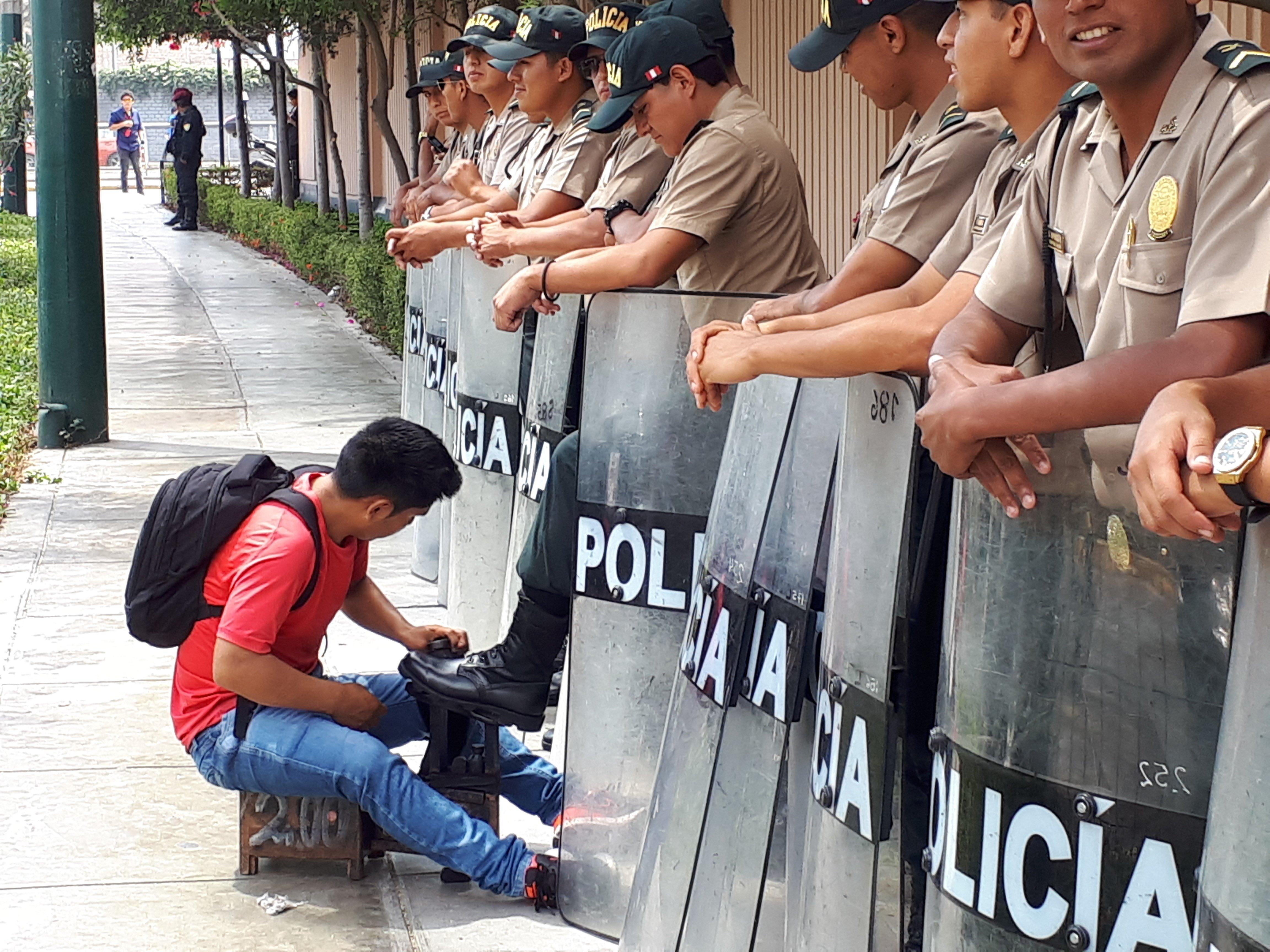 Un home neteja el calçat d'un policia als voltants de la seu de la VIII Cimera de les Amèriques, a Lima (Perú). /ELÍAS LEVY