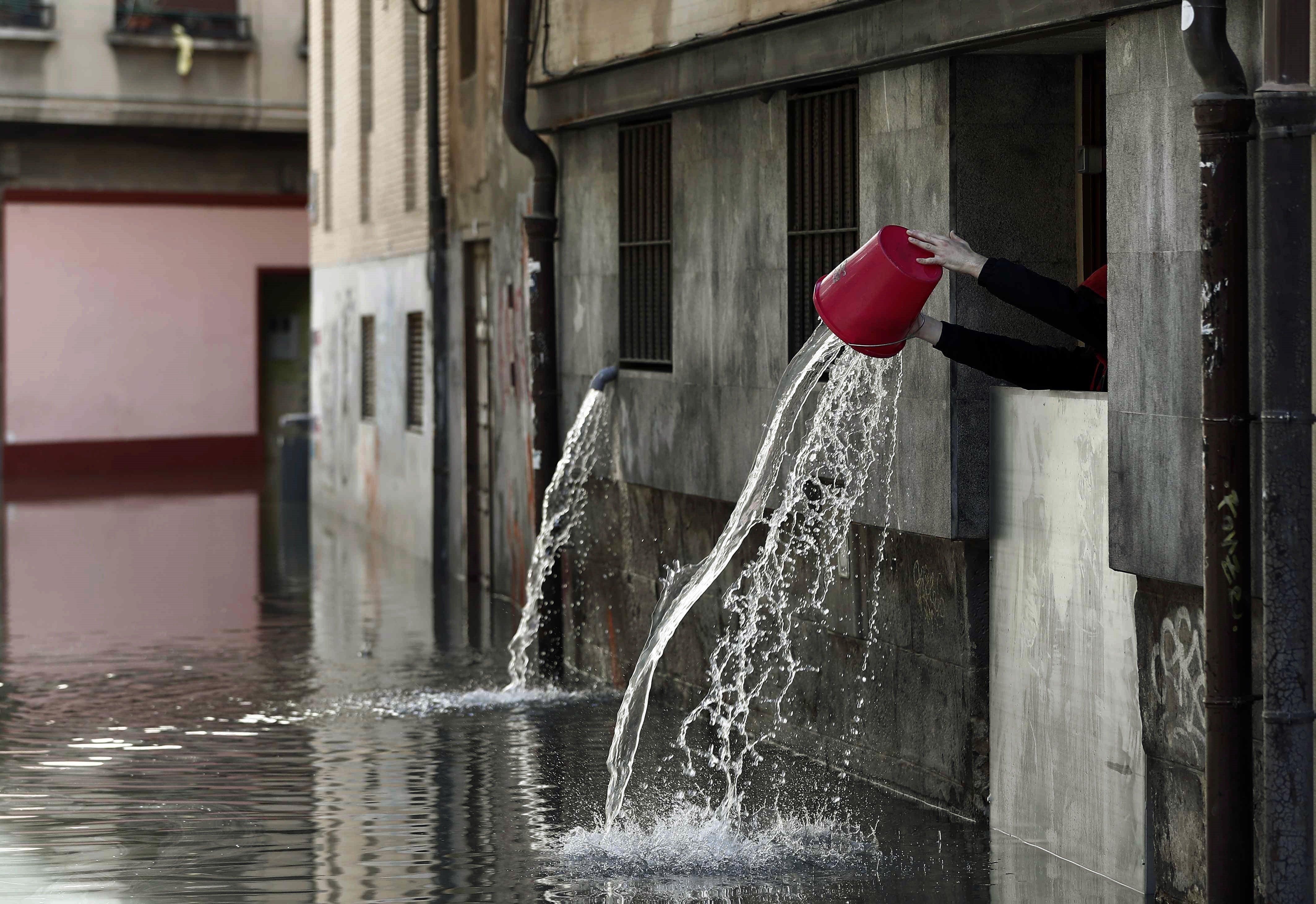 Una persona aboca l'aigua recollida que ha entrat a les cuines d'un restaurant de Tudela, després de la inundació que ha sofert el centre històric per la crescuda del riu Ebre. L'alerta per inundacions es manté encara a Navarra. /JESÚS DIGES
