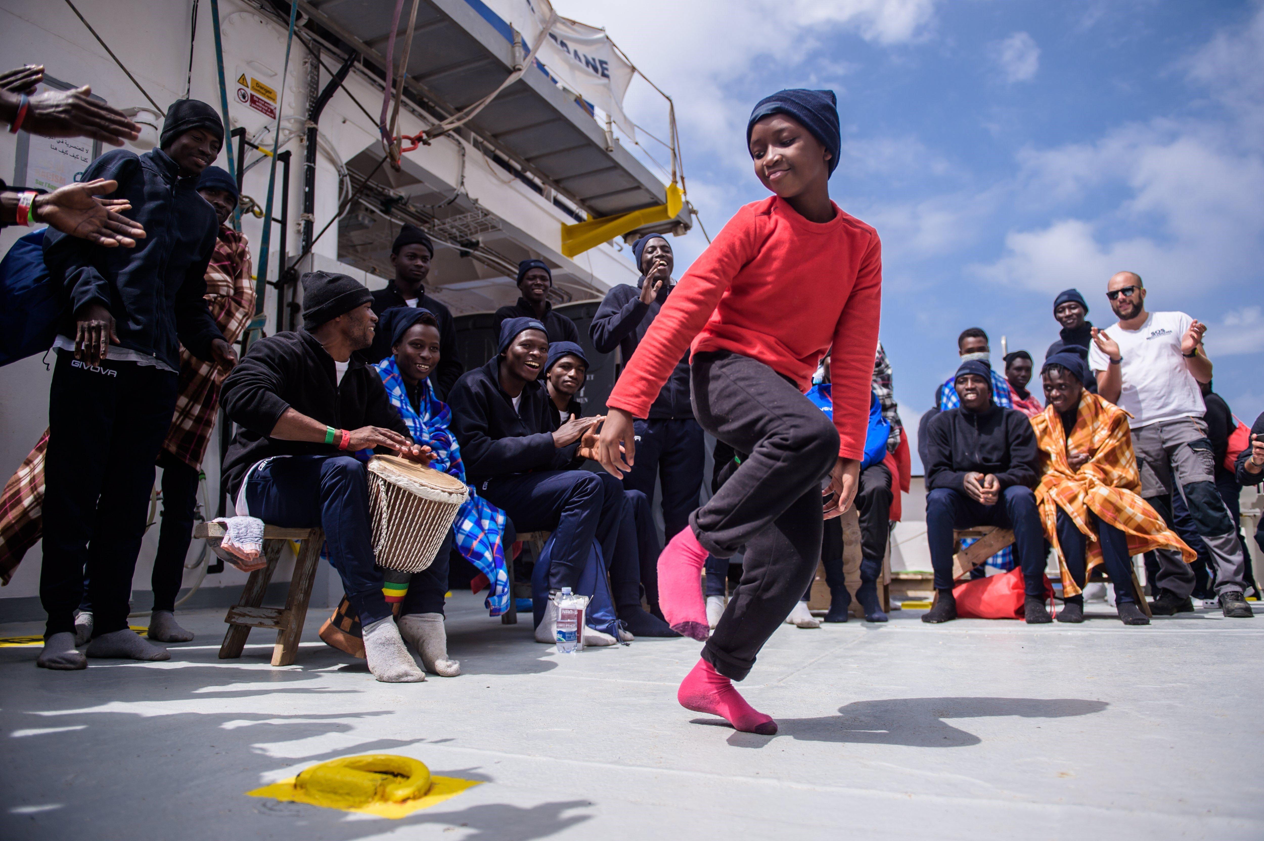 """Una nina balla al costat d'un grup d'immigrants a bord de l'embarcació """"Aquarius"""" un dia després de ser rescatats per membres de l'ONG """"SOS Mediterranée"""", durant una operació a uns 50 km de la costa de Líbia. Almenys 164 persones varen ser rescatades mentre intentaven arribar a Europa. /CHRISTOPHE PETIT TESSON"""