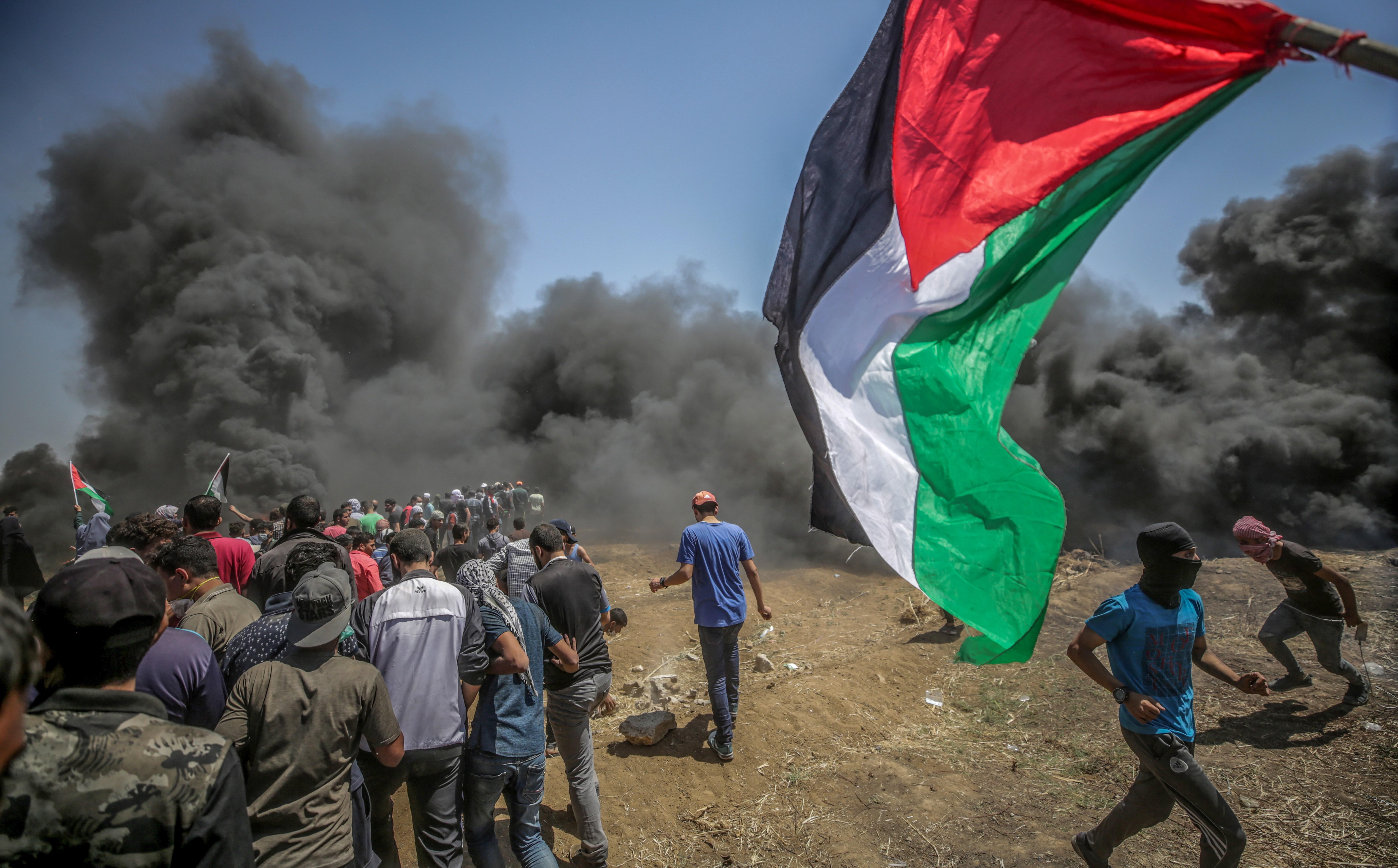 Manifestants corren per protegir-se del gas lacrimogen llançat per soldats israelians durant unes protestes a la frontera de Gaza i Israel. /MOHAMMED SABER