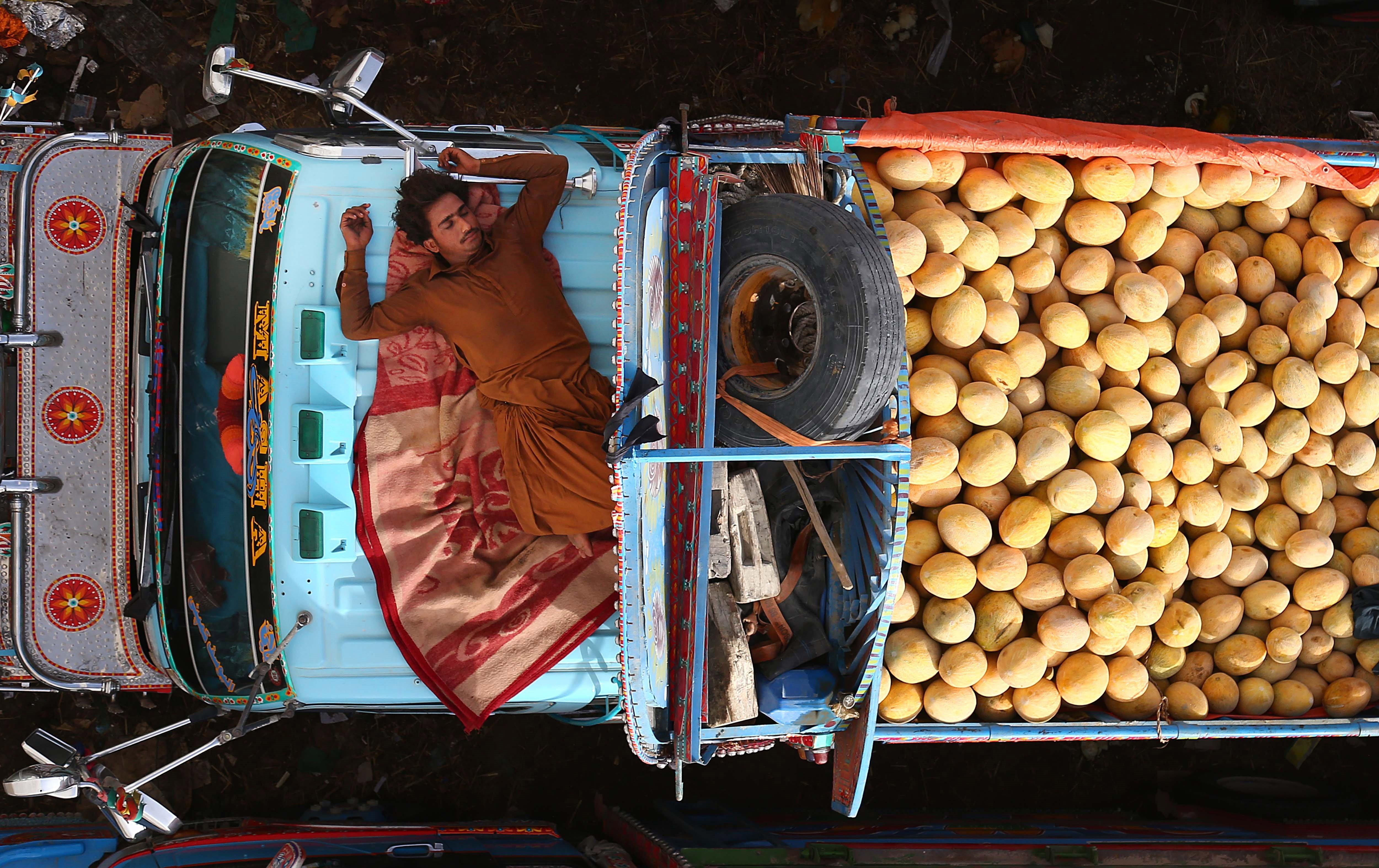 Un venedor fa una migdiada en la seva furgoneta on ven melons en un mercat a Karachi (Pakistan)  un dia abans del començament del Ramadà. /SHAHZAIB AKBER
