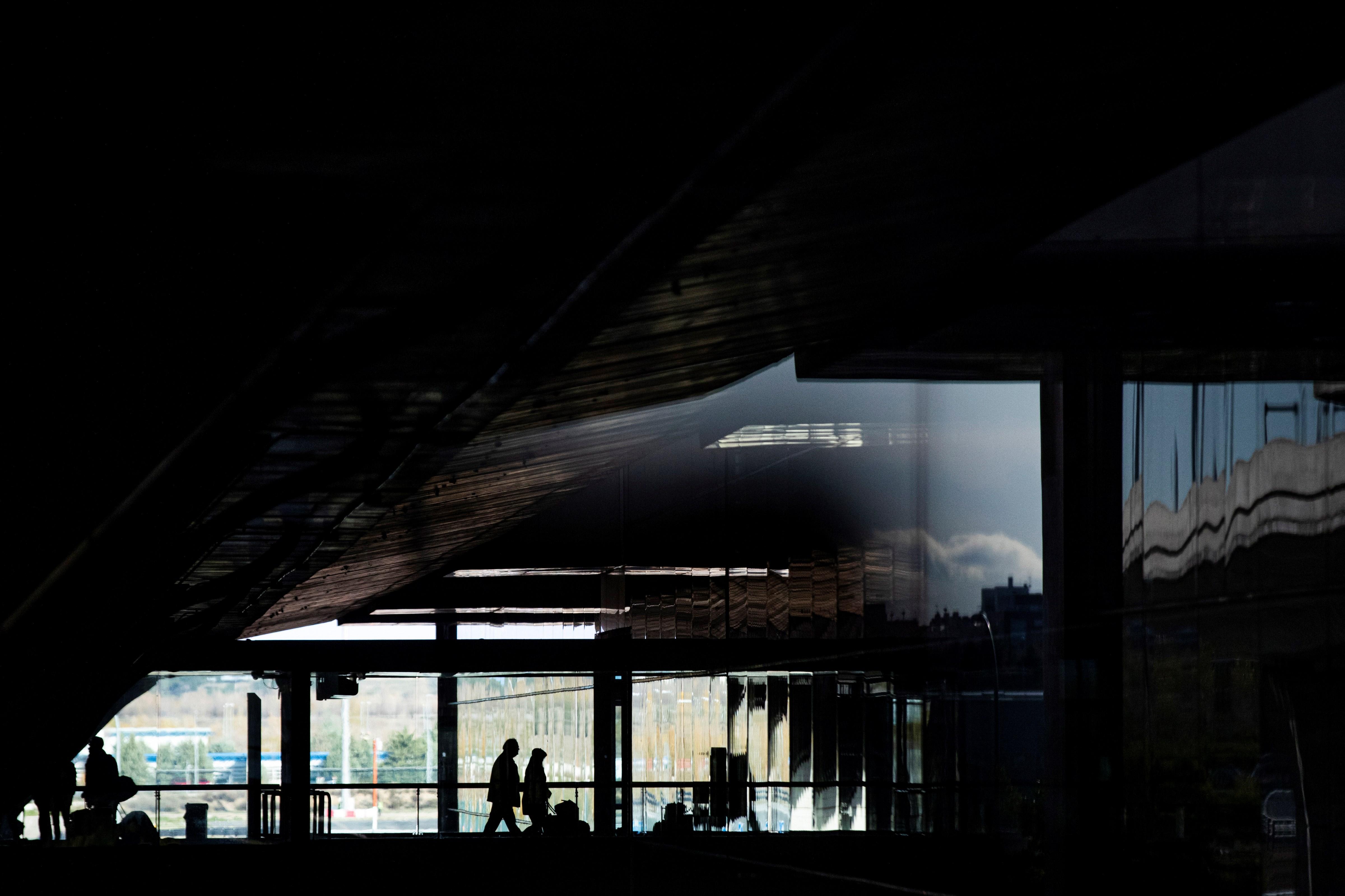 Diverses persones transiten per l'aeroport de Madrid-Barajas dijous a la vigília del pont de la Constitució. / EMILIO NARANJO